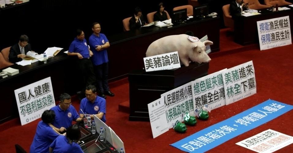 31.mai.2016 - Opositores do governo invadiram o salão principal do parlamento de Taiwan e colocaram um porco de brinquedo no local. Os manifestantes pediam o impedimento da importação de carne suína dos Estados Unidos que teria ractopamina, produto usado para o crescimento e engorda. Com o protesto, o novo premier Lin Chuan cancelou seu discurso sobre o relatório administrativo do parlamento