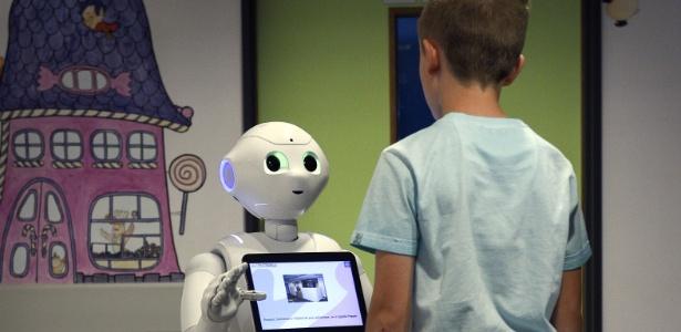 Garoto conversa com o robô Pepper no hospital La Citadelle, em Liège, Bélgica