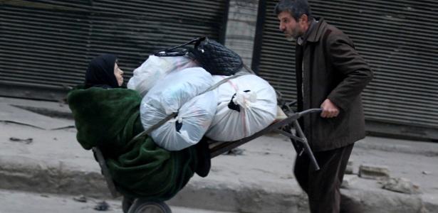 Homem carrega idosa e seus pertences durante fuga de Aleppo, na Síria