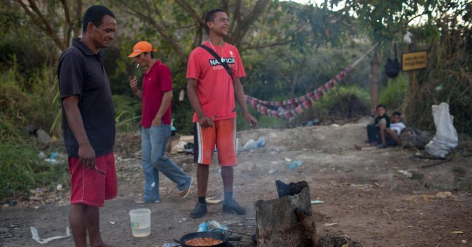 27.fev.2018 - Refugiados venezuelanos Harold Reyes, 42, e Jose Pena, 22, cozinham perto de Pacaraima, Roraima