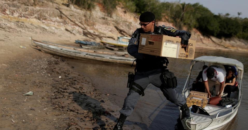21.out.2018 - Policial carrega caixa com urna eletrônuca em uma comunidade de ribeirinhos, à margem do Rio Negro, em Manaus