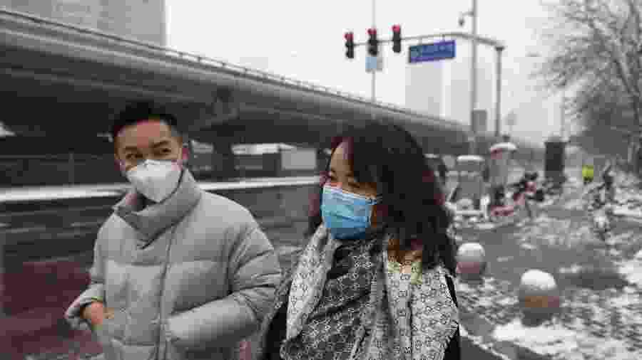 06.fev.2020 - Pessoas usam máscaras para circular numa rua deserta em Pequim; - Greg Baker/AFP