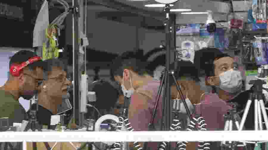 Pessoas usam máscaras de proteção para o coronavírus enquanto compram álcool gel em loja da Avenida Paulista, em São Paulo - Paulo Guereta/Agência O Dia/Estadão Conteúdo