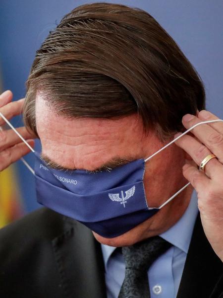 O presidente Jair Bolsonaro coloca máscara durante evento no Planalto, nesta segunda (22) - Ueslei Marcelino/Reuters