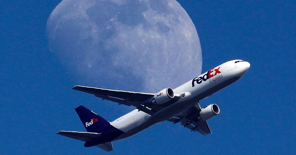 27.jul.2015 - Avião sobrevoa a cidade com a lua ao fundo, em direção ao aeroporto Internacional de Los Angeles, na Califórnia (Estados Unidos)