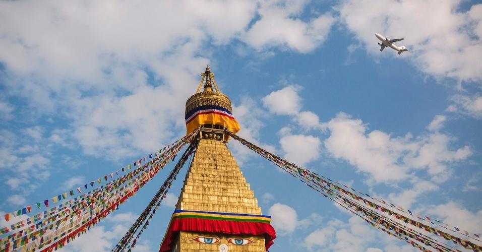 8.dez.2015 - Um avião sobrevoa o Boudhanath Stupa, em Katmandu, Nepal. Apesar de muitos monumentos terem sido destruídos no terremoto que atingiu a região em 2015, este templo budista resistiu sem grandes danos