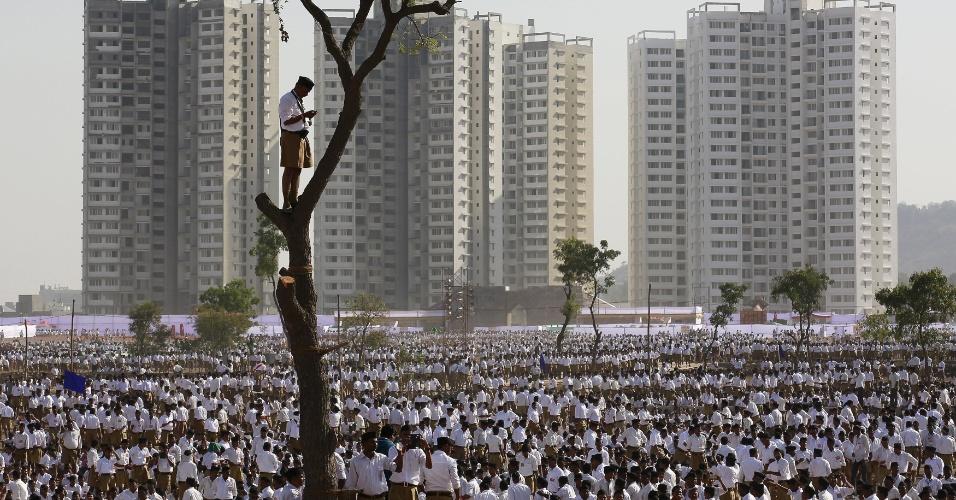 3.jan.2016 - Um voluntário da organização nacionalista hindu RSS (Rashtriya Swayamsevak Sangh) fica em pé em uma árvore na periferia de Pune, na Índia. Milhares de voluntários se reuniram para promover a organização e chamar a atenção da sociedade, segundo a mídia local. A organização tem 90 anos de idade e é considerada a maior ONG do mundo