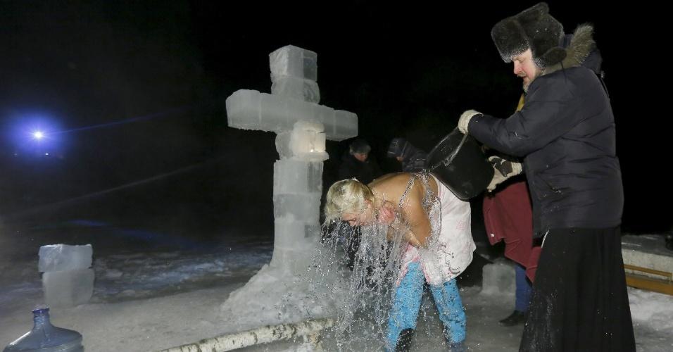18.jan.2016 - As cerimônias são lideradas por um sacerdote, como esta em um vilarejo da Sibéria, no rio Mano, que estava coberto de gelo. A temperatura do ar no momento desta imagem era de imperdoáveis -33º C