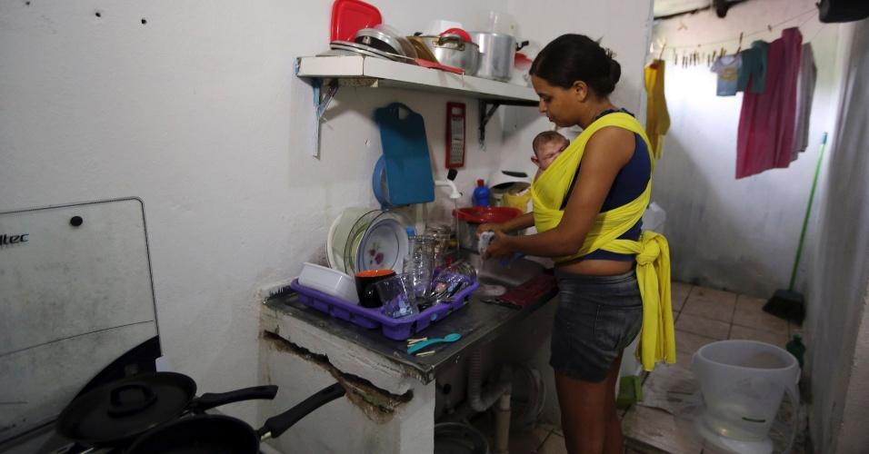 """A mãe Daniele Santos usa um """"Wrap Sling"""", pano utilizado para carregar bebês, enquanto lava a louça. Além do tratamento convencional num hospital de Recife, o filho Juan Pedro, que tem microcefalia, agora conta com o apoio do """"Espaço para ser Mãe"""", grupo maternal que realiza workshops para mães de crianças com problemas de nascença relacionados à zika, ensinando técnicas naturais para apaziguar as crianças -- entre elas, a massagem indiana, conhecida como shantala"""