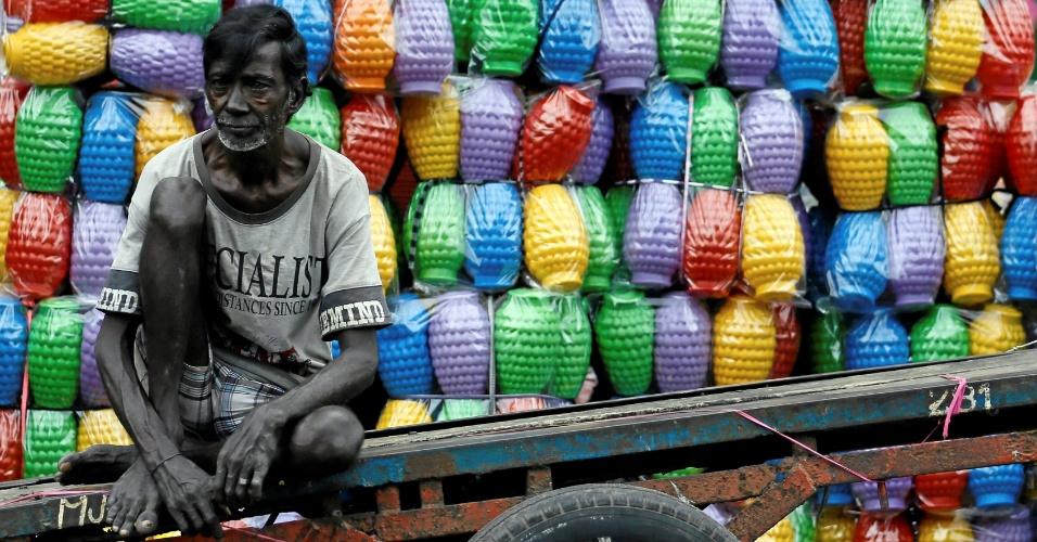 23.set.2016 - Trabalhador descansa após descarregar jarras de plástico em mercado de Colombo, no Sri Lanka