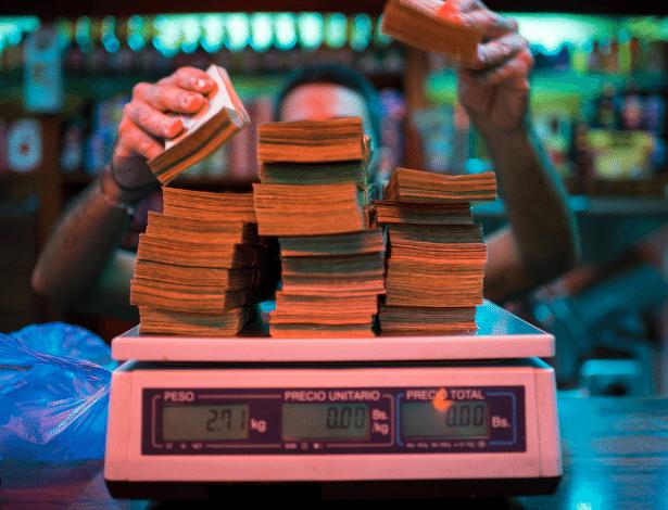 Gerente de padaria pesa notas de dinehiro em Caracas, na Venezuela
