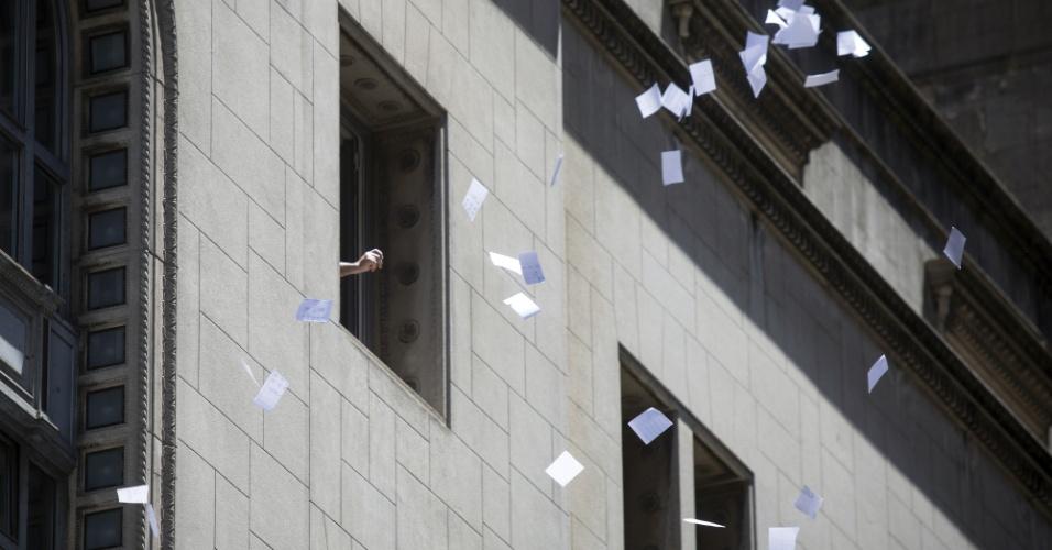 30.dez.2016 - Funcionário atira papéis pela janela de um dos escritórios de um banco em Buenos Aires, na Argentina. É tradição no microcentro portenho lançar papéis da janela no último dia útil do ano