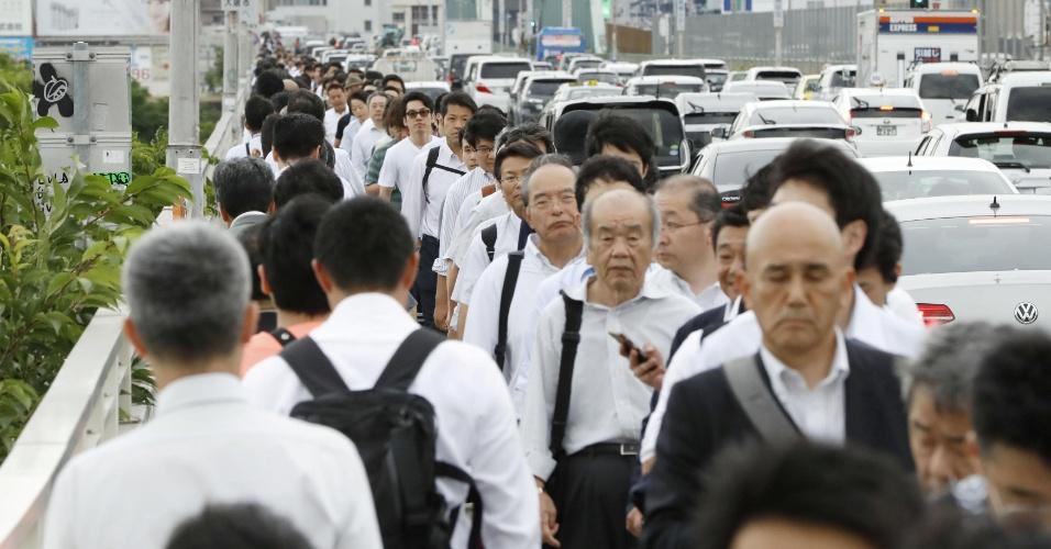 18.jun.2018 - Pessoas caminham em ponte sobre rio Yodo após o transporte público ser interrompido por causa de danos causados pelo terremoto em Osaka