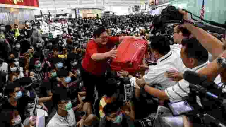 Alguns se esforçaram para passar por multidões antes que os voos fossem suspensos - AFP