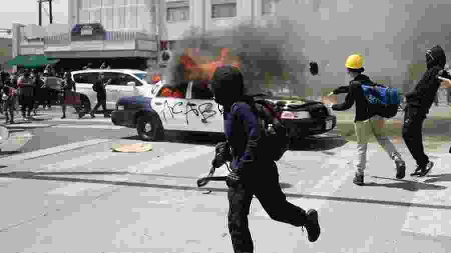 Oficiais da tropa de choque e manifestantes que atearam fogo em viaturas entraram em confronto em Los Angeles, na Califórnia - Getty Images