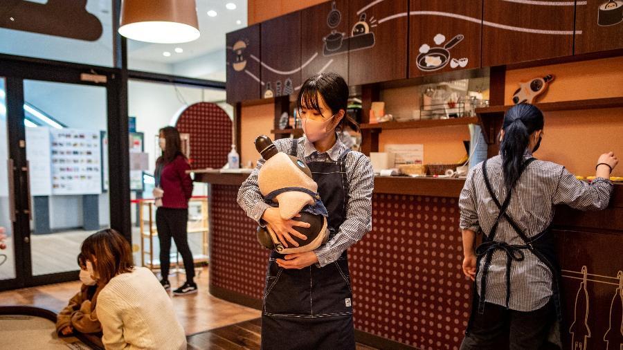 Nesta foto tirada em 20 de dezembro de 2020, uma atendente segura um robô Lovot em um café em Kawasaki - PHILIP FONG / AFP
