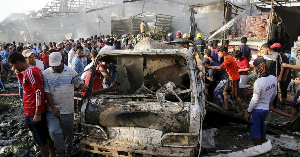 13.ago.2015 - Moradores e curiosos se reúnem nesta quinta-feira no local de atentado terrorista com um caminhão-bomba em um mercado lotado em Bagdá. Pelo menos 60 pessoas morreram e 200 ficaram feridos quando um caminhão refrigerado carregado de explosivos explodiu no mercado de Sadr, bairro xiita no nordeste da capital iraquiana. O Estado Islâmico, grupo terrorista sunita, reivindica a autoria do ataque