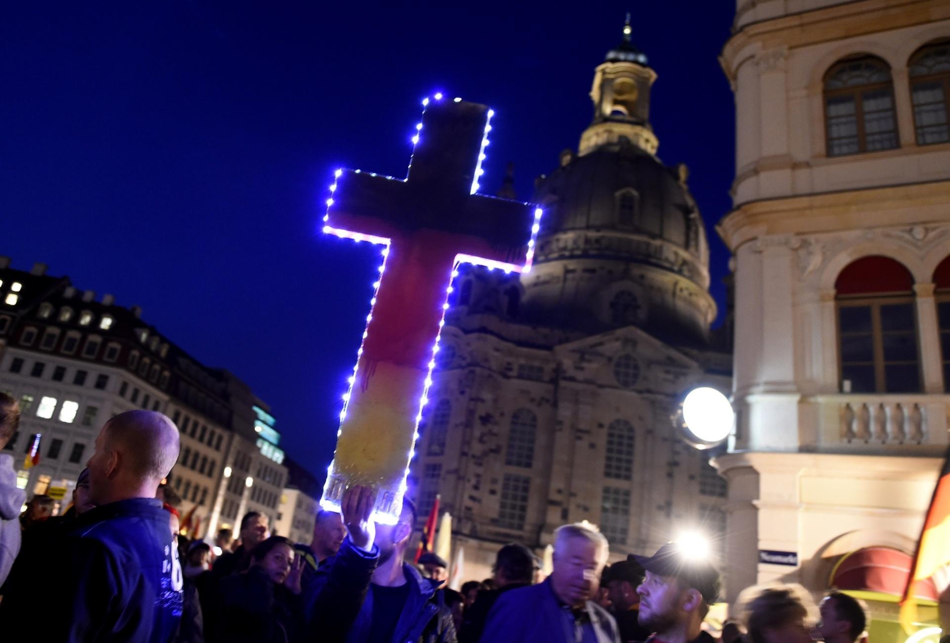 5.out.2015 - Manifestante ergue cruz pintada com as cores da bandeira da Alemanha durante protesto na cidade de Dresden contra a entrada maciça de refugiados no país. A manifestação reuniu quase dez mil pessoas e foi convocada pelo movimento Pegida (Patriotas Europeus contra a Islamização do Ocidente, em alemão)