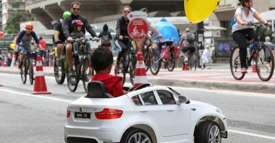 18.out.2015 - Menino aproveita o fechamento da avenida Paulista para veículos para brincar com o seu carro. Depois de dois testes realizados em junho e agosto, a prefeitura decidiu fechar a via para carros aos domingos, das 9h às 17h