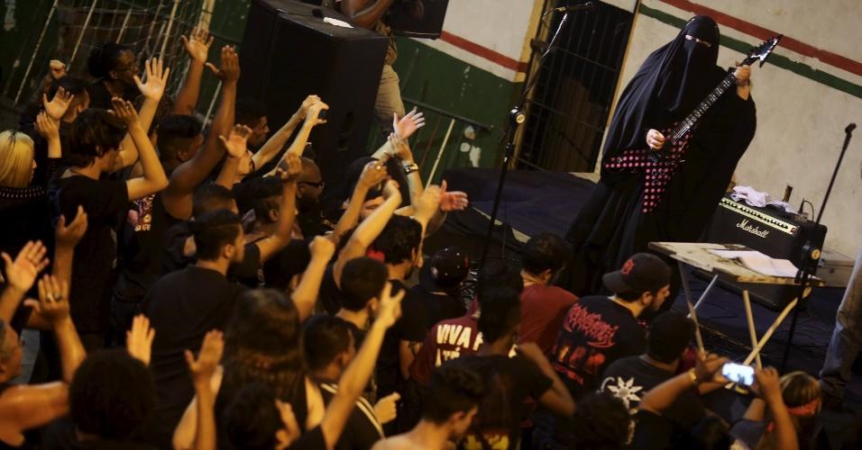 """9.nov.2015 - A muçulmana Gisele Marie, 42, toca guitarra em um show de heavy metal para arrecadar fundos para refugiados sírios no Rio de Janeiro. Marie mora em São Paulo e é filha de alemães católicos, mas se converteu ao islamismo meses após o pai morrer, em 2009. Desde 2012, Ela está à frente da banda de heavy metal dos irmãos chamada de """"Spectrus"""". ?As pessoas não esperam ver uma mulher muçulmana que usa burca, praticante da religião, sendo guitarrista profissional que toca em uma banda de heavy metal. Muitos ficam chocados?, contou. A imagem foi feita no domingo (8)"""