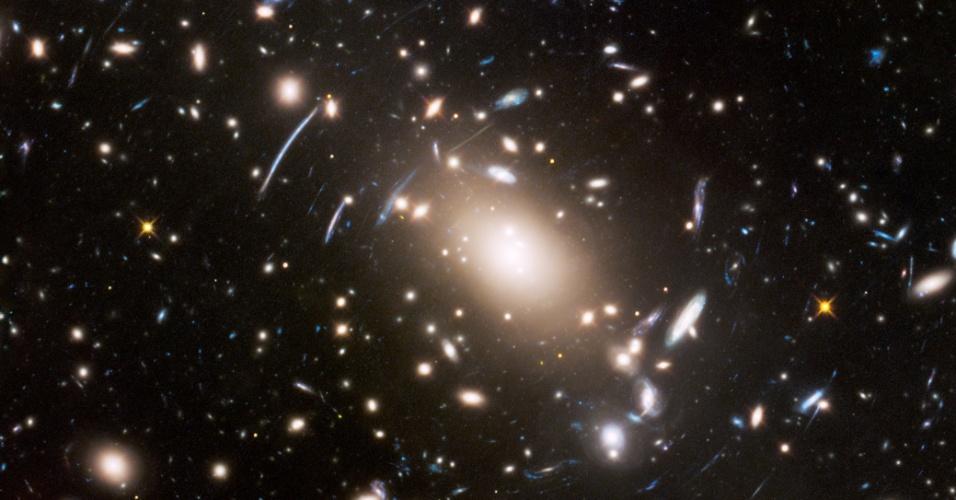 """21.jul.2016 - TRUQUE DE LUZ - Foto feita pelo telescópio espacial Hubble mostra um aglomerado de galáxias em um """"Universo desordenado"""", a cerca de quatro bilhões de anos-luz de distância. Na foto, vê-se uma deformação do espaço, por causa do efeito de lente gravitacional. A enorme massa do aglomerado distorce e amplia a luz das galáxias distantes, ajudando cientistas a estudá-las"""