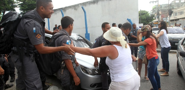Mulheres de policiais militares protestam em frente ao portão da Coordenadoria de Polícia Pacificadora em Ramos