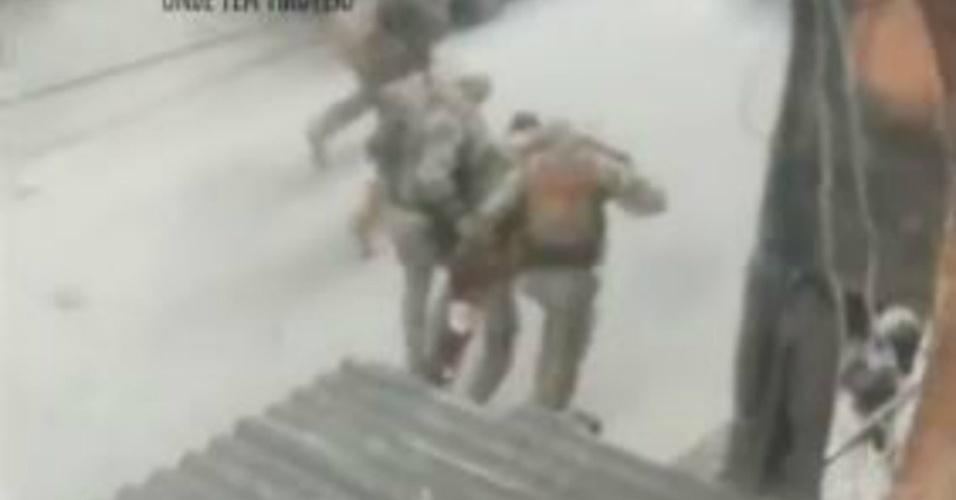 Policial é carregado por colegas para fora da Cidade de Deus