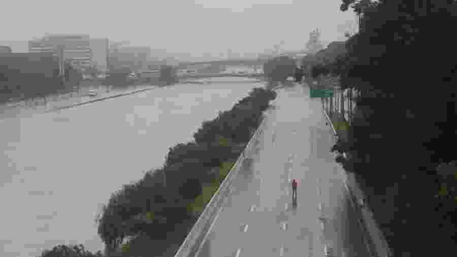 Homem caminha por pista interditada da Marginal Tietê durante dia de alagamentos em São Paulo - Rahel Patrasso/Reuters