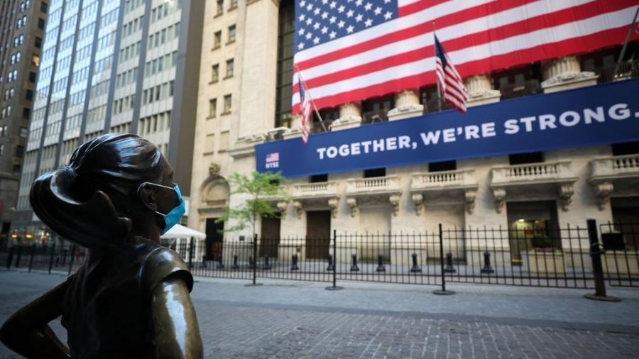 """26.mai.2020 - De máscara, estátua da """"Fearless Girl"""" é colocada em frente ao prédio do New York Stock Change, em Nova York (EUA) - Tayfun Coskun/Anadolu Agency via Getty Images"""