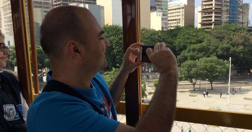 27.jul.2015 - O turista gaúcho Luciano Boeira, 42, tira foto com o celular enquanto o bondinho de Santa Teresa passa por cima dos Arcos da Lapa, no centro do Rio de Janeiro, na manhã desta segunda-feira (27), primeiro dia de pré-operação do sistema