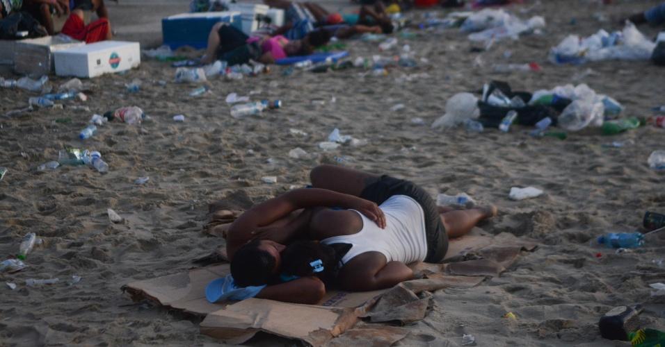 1º.jan.2016 - Casal dorme entre o lixo deixado na areia da praia de Copacabana, na zona sul do Rio de Janeiro, na manhã do primeiro dia de 2016, após a tradicional festa de Réveillon