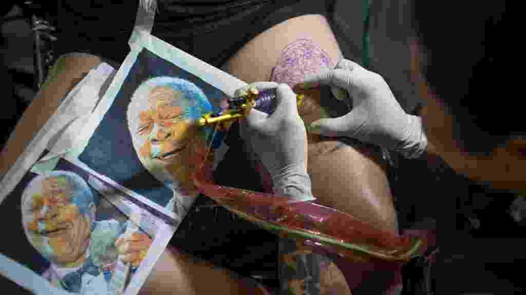 22.jan.2016 - Está pensando em fazer uma tatuagem? Saiba que a tendência do momento são os desenhos realistas, ou seja, aqueles que utilizam técnicas de luz e sombras na pele. Na imagem, o tatuador Denis Kakazu reproduz uma fotografia do guitarrista e cantor norte-americano B.B King, no primeiro dia da Convenção Internacional Tattoo Week 2016, que acontece no  Centro Sulamérica, em Cidade Nova, Rio de Janeiro (RJ) - Mauro Pimentel/UOL
