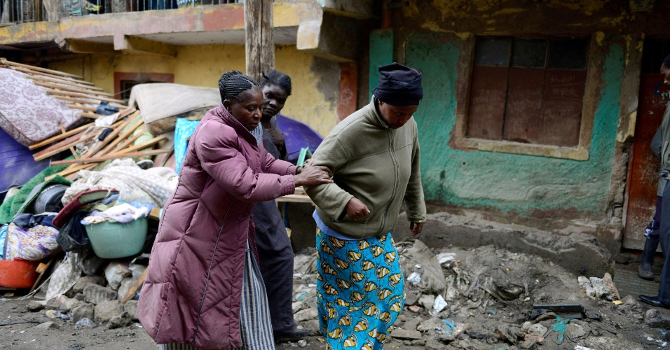 30.abr.2016 - Mulher é auxiliada após edifício em bairro pobre de Nairobi, Quênia, desabar em decorrência de fortes chuvas. Dez pessoas foram confirmadas mortas