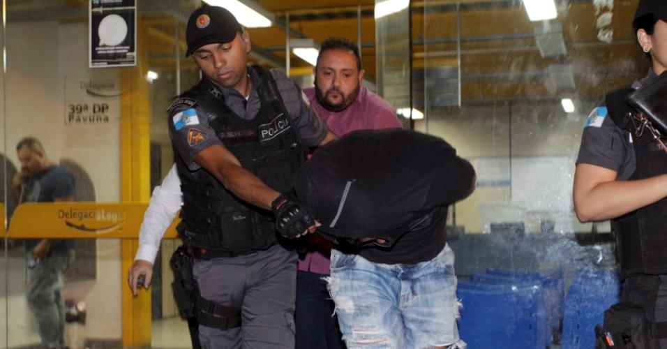 5.mai.2017 - Policial militar suspeito de fornecer armas para traficantes chega à 39ª DP (Pavuna), no Rio de Janeiro, após ter sido preso junto com um homem que, de acordo com a polícia, seria um dos principais fornecedores de armas e munições para facções criminosas