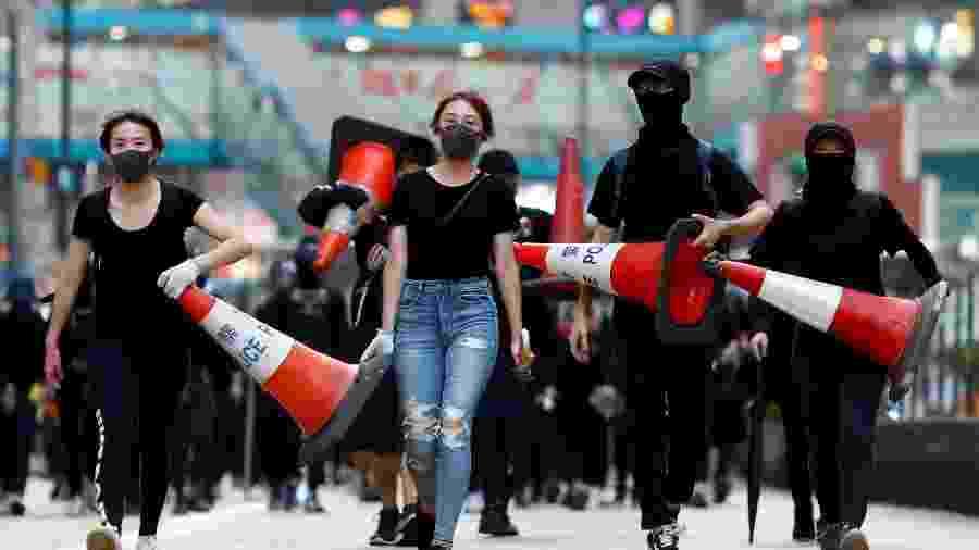 Manifestantes caminham durante protesto em Causeway Bay, área de Hino Kong conhecida pelas lojas caras - Thomas Peter/Reuters