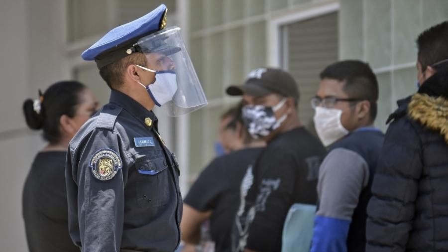28.04.2020 - policial vistoria fila em frente a hospital na Cidade do México durante a pandemia do novo coronavírus - Pedro Pardo/AFP