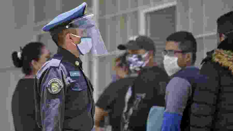 28.04.2020 - Policial vistoria fila em frente a hospital na Cidade do México durante pandemia do novo coronavírus - Pedro Pardo/AFP