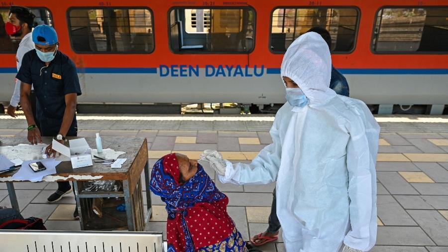 14.abr.2021 - Trabalhadora da saúde coleta amostra para teste de coronavírus de passageira em plataforma ferroviária em Mumbai, na Índia - Punit Paranjpe/AFP