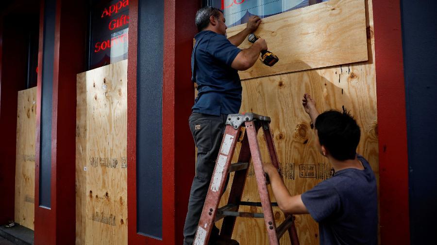 Trabalhadores colocam tapumes de madeira para proteger as vitrines de uma loja do furacão Ida, em New Orleans, nos EUA - Marco Bello/Reuters