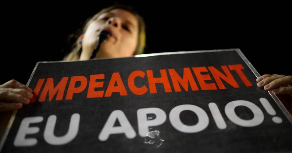 """15.abr.2016 - Manifestante segura cartaz a favor do impeachment da presidente Dilma Rousseff durante ato em frente ao Congresso Nacional, no espaço do """"muro da vergonha"""" reservado aos protesto contra a presidente"""
