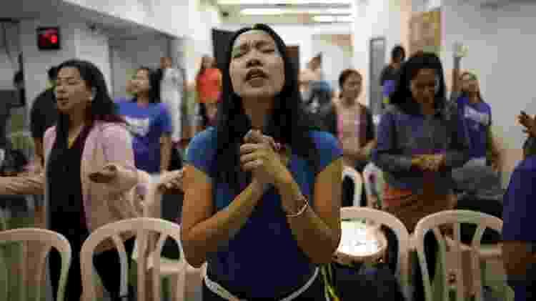 Merry Christ Palacios, 37 anos, uma cuidadora das Filipinas, ora durante um culto realizado na Estação Rodoviária Central em Tel Aviv, Israel - Corinna Kern/Reuters