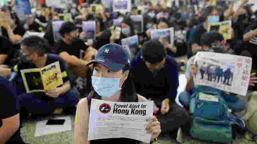 Manifestantes seguram cartazes na área de chegada do Aeroporto Internacional de Hong Kong para que turistas leiam - Thomas Peter/Reuters