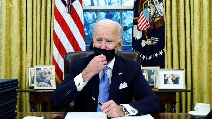 O presidente dos EUA, Joe Biden, ajusta a máscara enquanto assina uma ordem executiva - Tom Brenner/Reuters