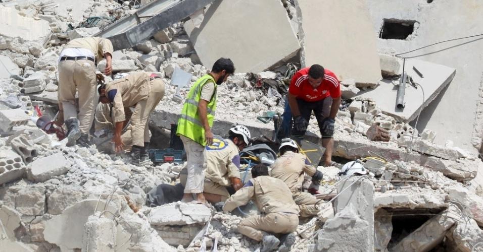 3.ago.2015 - Equipes da defesa civil e voluntários procuram por sobreviventes sob os escombros após a queda de um avião militar em Ariha, na Síria. O acidente deixou dezenas de mortos e feridos
