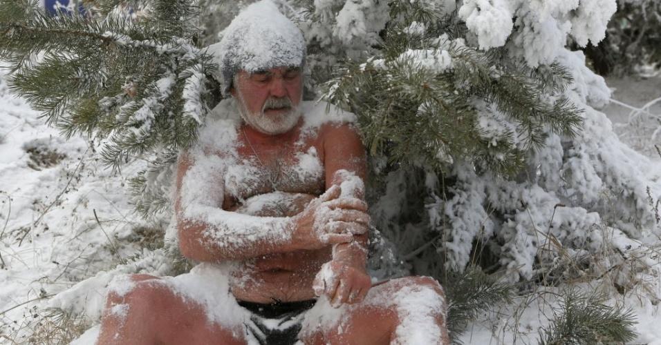 """6.jan.2015 - Nikolai Bocharov, 77, integrante do clube Cryophile de nadadores de inverno, cobre seu corpo com neve depois de banhar-se nas águas geladas do rio Yenisei, em Krasnoyarsk, na Rússia. A temperatura no momento da brincadeira era de -27°C. Bocharov conta que começou a nadar no frio do inverno quando serviu o Exército na Alemanha. """"Quando voltei para casa, fiz um buraco no gelo do rio Yenisei e me banhei nele"""", conta. """"Nunca peguei nenhum resfriado e posso ficar em água gelada por bastante tempo. Quando saio da água gelada, sinto uma sensação de formigamento em todo o meu corpo. É como se estivesse pronto para voar"""", diz"""