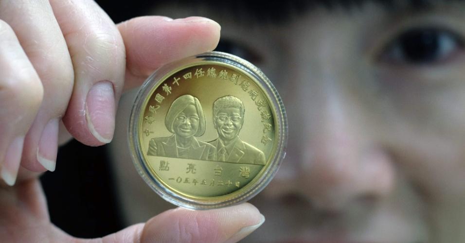11.mai.2016 - Mulher exibe moeda de ouro que retrata a presidente e o vice-presidente recém-eleitos em Taiwan, Tsai Ing-wen e Chen Chien-jen, respectivamente