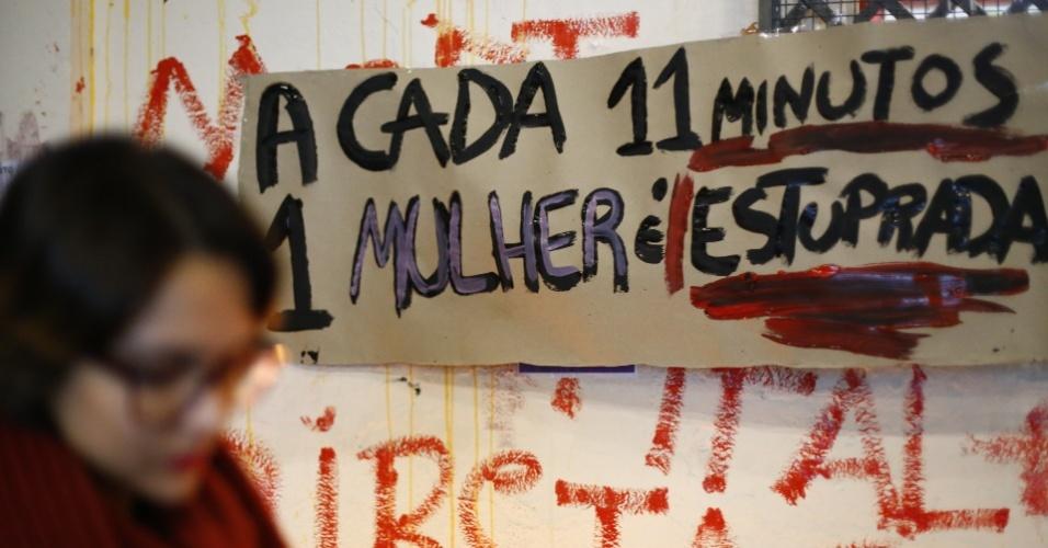 30.mai.2016 - Estudante universitária da PUC (Pontifícia Universidade Católica) de São Paulo passa por cartaz de uma manifestação contra o assédio e a cultura do estupro no campus da universidade