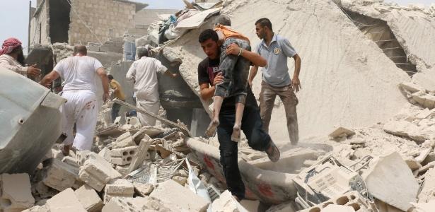 Homem carrega criança ferida em bombardeio no bairro de Bab al-Nairab, em Aleppo, na Síria