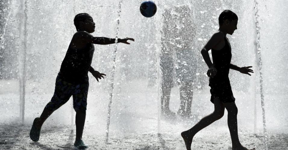 26.ago.2016 - Duas crianças brincam em fonte num dia quente em Frankfurt (Alemanha)