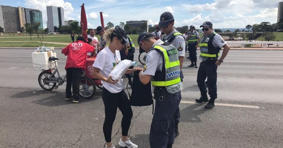26.mar.2017 - Policiais revistam pertences de manifestantes em Brasília